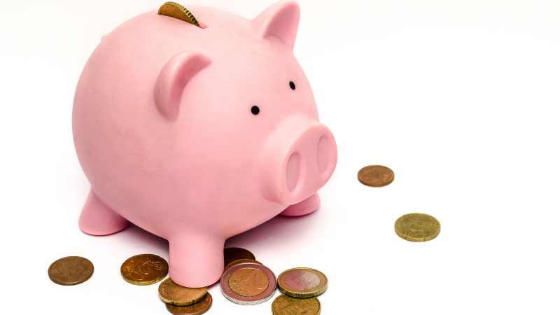 A pink piggy bank with coins on the floor