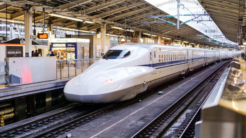 a bullet train pulling into a train station in Japan