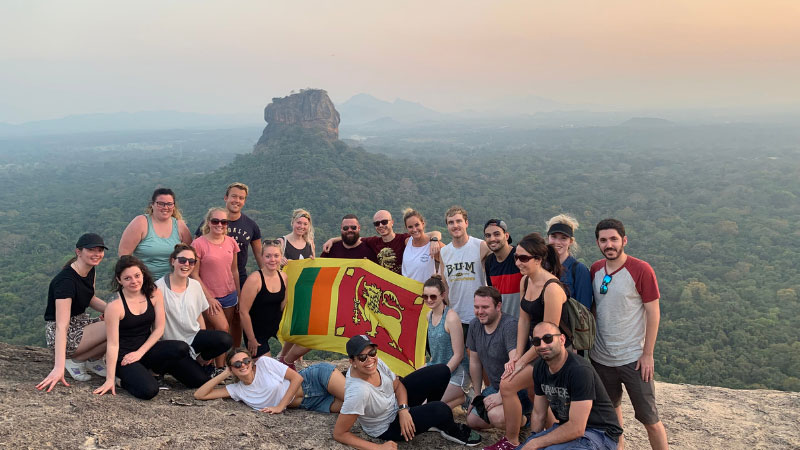 One for life adventures tour group sitting at the top of Pidurangala rock in sri lanka