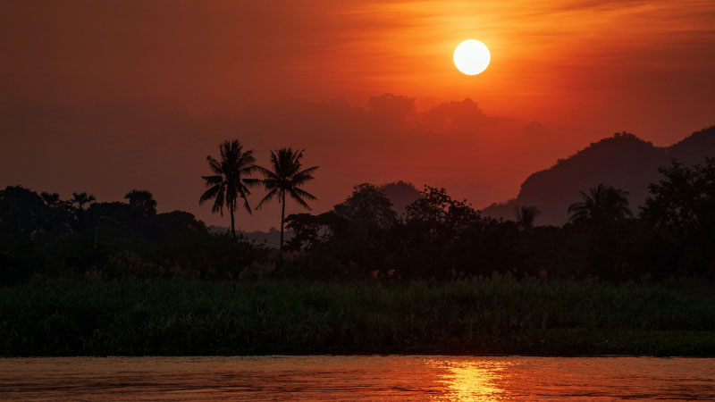 The sun setting over a river