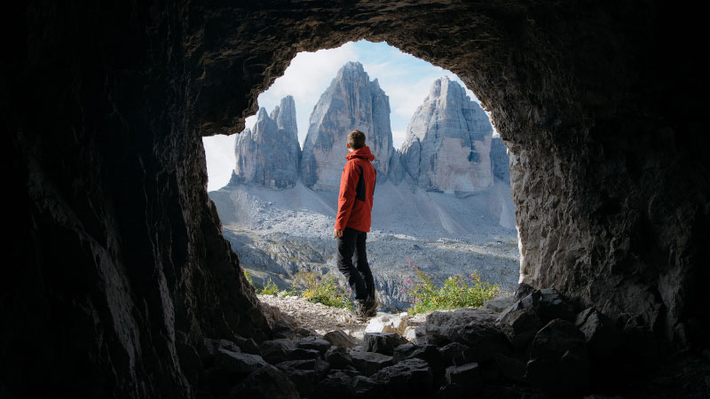A photograph taking at a very low angle of a man looking out into the mountains
