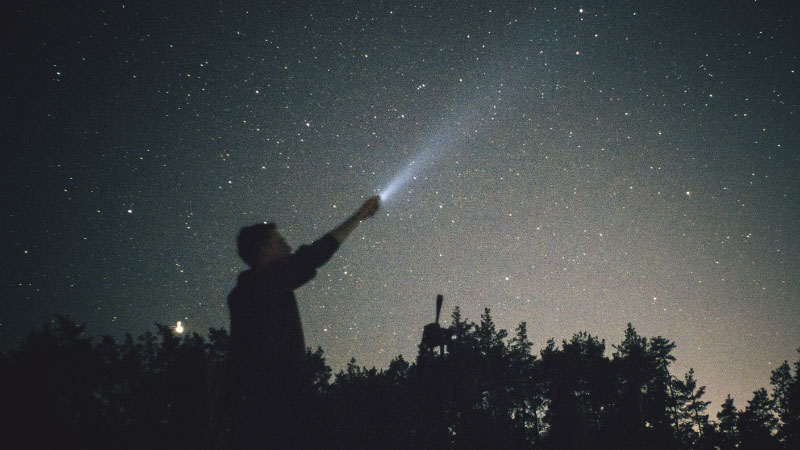 a person holding a torch up to the night sky