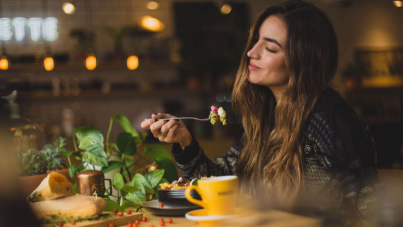 woman eating pasta alone at a table