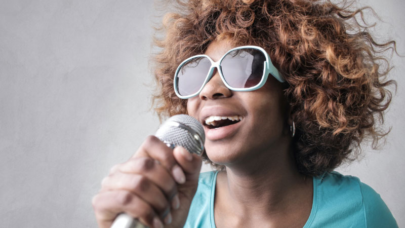 a woman singing karaoke with a microphone