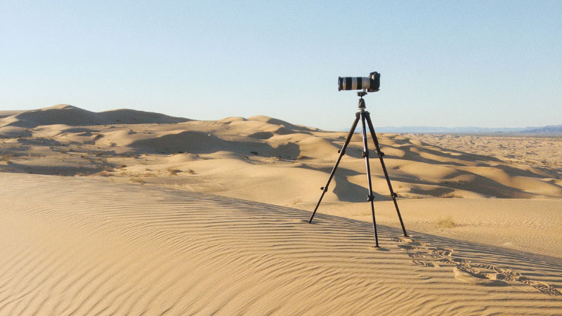 A camera sitting on a tripod in the desert
