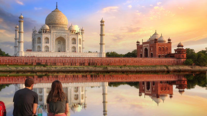 couple sitting in front of the taj mahal in india